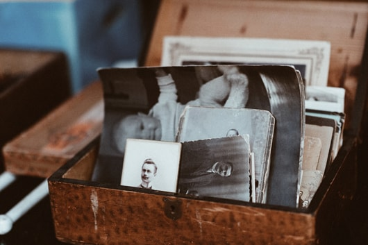 An small and antique looking wooden box with old, monochrome photographs in it.