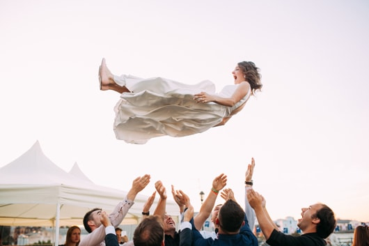 A bride thrown in the air by her guests.