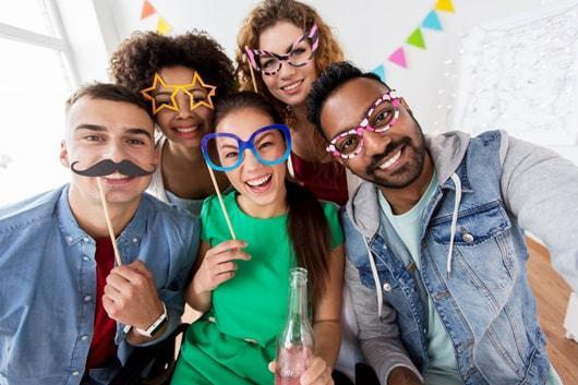 Party guests wearing fake glasses and mustaches made from cardboard taking a selfie.