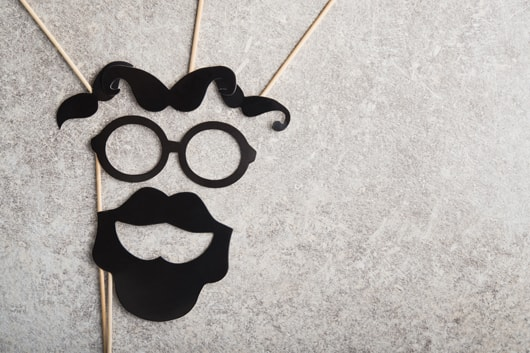 A face made up from cardboard requisites. Mustaches for eyebrows, a pair of glasses for outlining the eyes and a full beard to outline the mouth.
