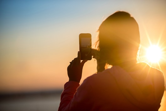 The silhouette of a person from behind, taking a picture of the setting sun in the background.